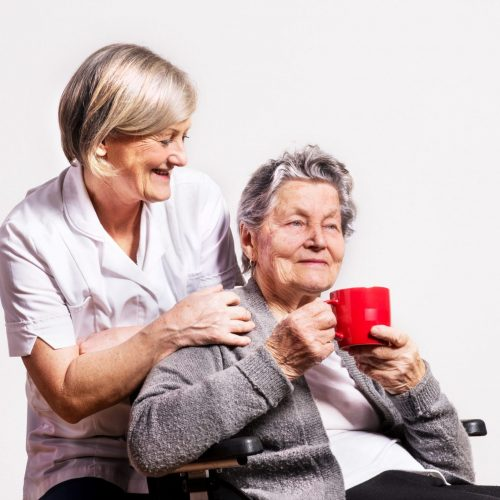Studio portrait of a nurse and a senior woman in wheelchair holding a red cup.