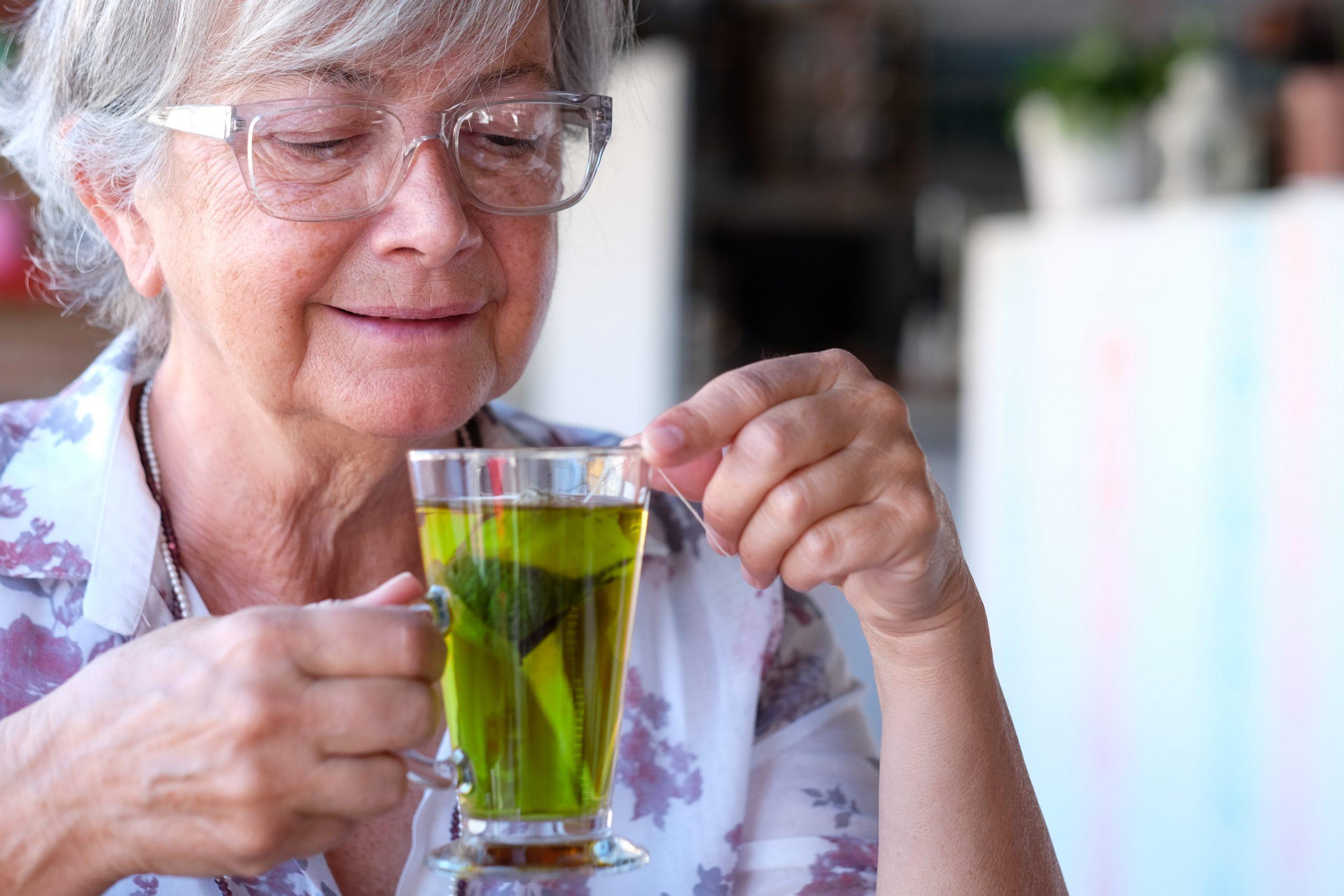 Alone senior woman drinking a herbal tea